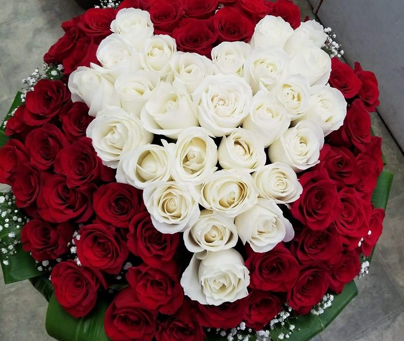 Red rose bouquet with white rose heart arrangement in center.